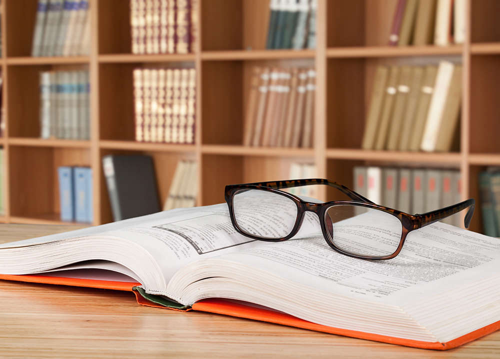 Glasses on top of book; books on shelves